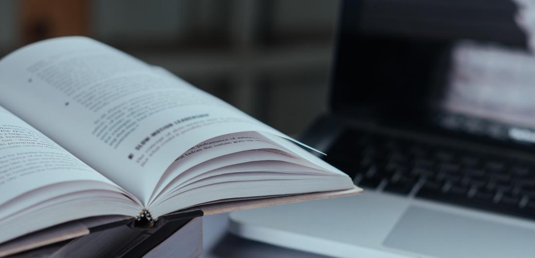libros apilados y ordenador portátil