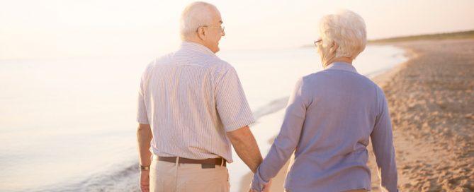 dos personas mayores caminan por la playa cogidos de la mano