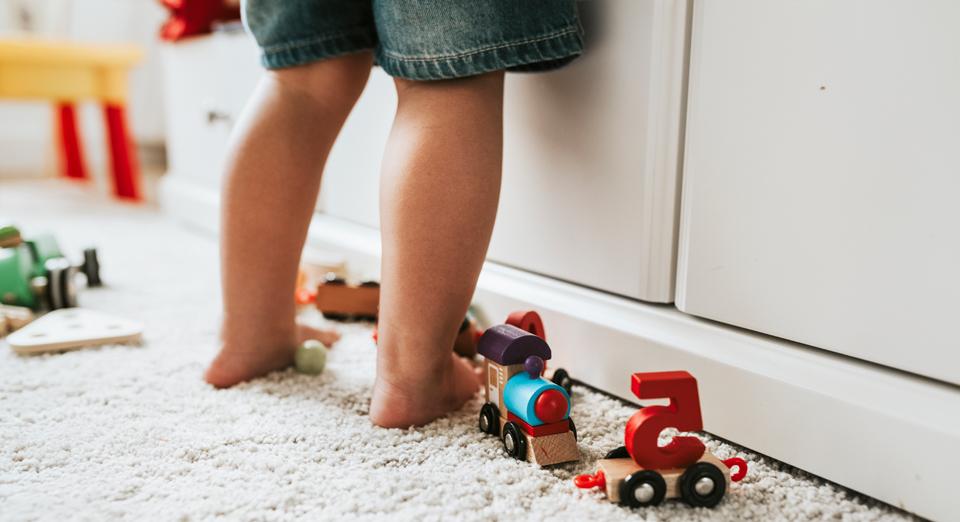 Las piernas de un niño en su habitación con juguetes.