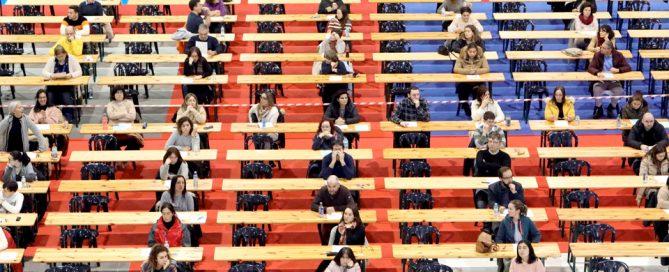 Personas sentadas en mesas preparadas para el examen de oposición
