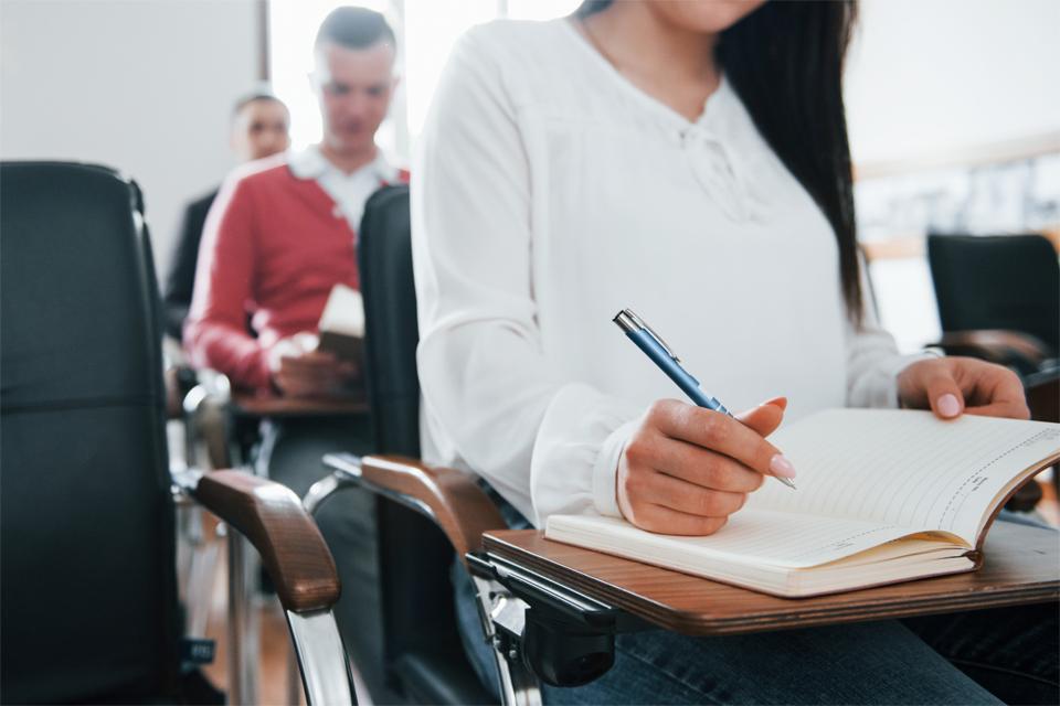 grupo de personas en el aula con bloc de notas y bolígrafo en manos