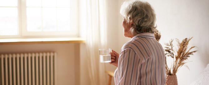 persona mayor de espaldas mirando hacia la ventana