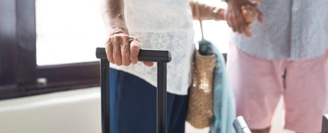 Pareja de personas mayores con maletas