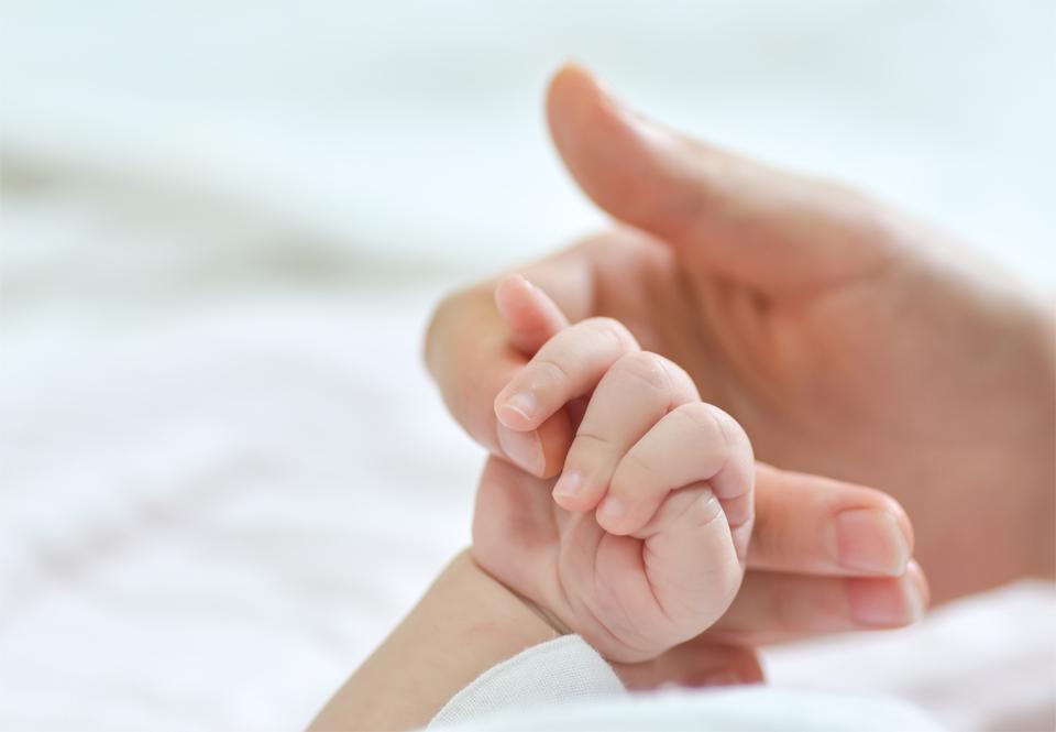 Mano de mujer sostiene la mano de su hijo