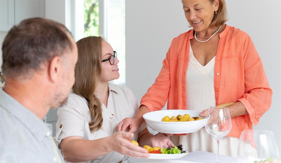 Padres con su hija con platos en la mesa