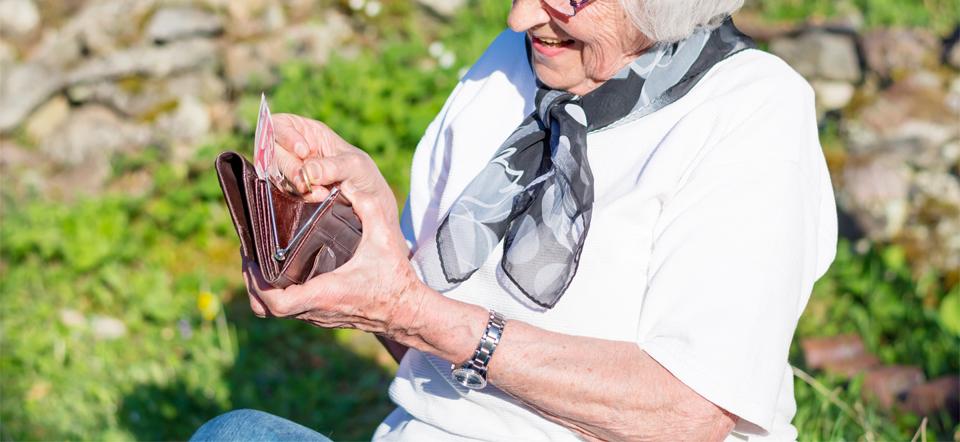 Mujer mayor con un monedero en la mano