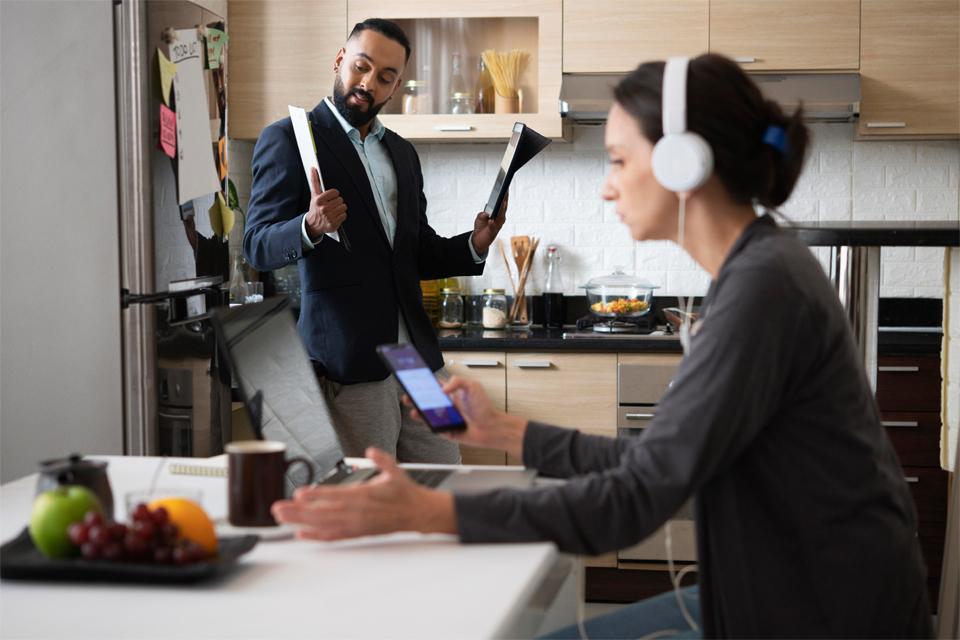 Dos personas en la cocina teletrabajando